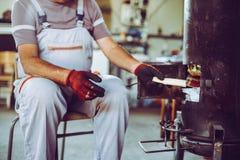 Älterer Mann in der Werkstatt Mann lag Feuer in der Werkstatt Lizenzfreies Stockbild