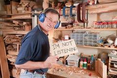 Älterer Mann in der Werkstatt nicht hörend Lizenzfreie Stockfotografie