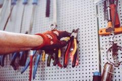 Älterer Mann in der Werkstatt Mann nimmt Zangen der Wolle Lizenzfreie Stockfotografie