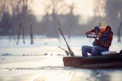 Älterer Mann der Winterjahreszeit, der auf gefrorenem See- und Getränktee sitzt Lizenzfreies Stockbild