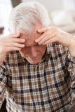 Älterer Mann, der zu Hause betont schaut Lizenzfreies Stockfoto