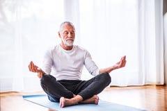 Älterer Mann, der zu Hause meditiert Stockfotografie