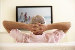 Älterer Mann, der zu Hause mit großem Bildschirm fernsieht Stockfotos