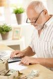 Älterer Mann, der zu Hause Taschenrechner verwendet Lizenzfreie Stockfotografie