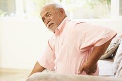 Älterer Mann, der zu Hause unter den rückseitigen Schmerz leidet Stockfotografie