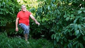 Älterer Mann in der zufälligen Kleidung, möglicherweise in einem Pensionär, Übungen oder Gymnastik im Hinterhof oder im Garten tu stock video