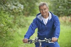 Älterer Mann, der Zyklus-Fahrt in der Landschaft genießt Lizenzfreie Stockbilder