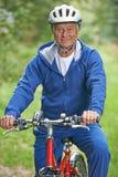 Älterer Mann, der Zyklus-Fahrt in der Landschaft genießt Lizenzfreies Stockbild