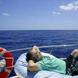 Älterer Mann des Seemanns, der einen Rest auf Sommerboot hat Stockbild