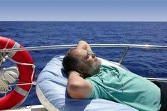 Älterer Mann des Seemanns, der einen Rest auf Sommerboot hat Stockfotografie
