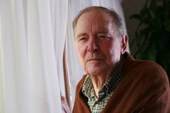 Älterer Mann durch Fenster mit ernstem Ausdruck Stockfoto