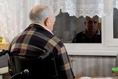 Älterer Mann in einem Rollstuhl, der an einem Fenster wartet Stockfotos