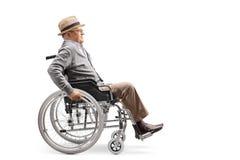 Älterer Mann in einem Rollstuhl, der sich manuell drückt stockfotos