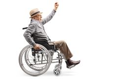 Älterer Mann in einem Rollstuhl, der sich manuell drückt und oben eine Hand anhebt stockfotografie