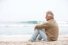 Älterer Mann am Feiertag, der auf Winter-Strand sitzt Lizenzfreie Stockfotografie