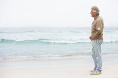 Älterer Mann am Feiertag, der auf Winter-Strand steht lizenzfreies stockfoto