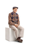 Älterer Mann gesetzt auf einem Würfel stockbild