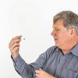 Älterer Mann hält Hörgerät Stockbild