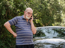 Älterer Mann am Handy in der Straße nahe bei Auto ruft um Hilfe Lizenzfreie Stockfotos