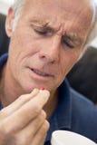 Älterer Mann-Holding-Pille Stockfoto