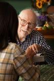 Älterer Mann im Haus mit Versorger oder Übersichtsabnehmer lizenzfreie stockbilder