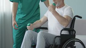 Älterer Mann im Rollstuhl, der Arme mit den Dummköpfen, unterstützt von der Krankenschwester, Rehabilitation biegt
