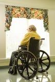 Älterer Mann im Rollstuhl durch Window stockfotografie
