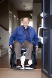 Älterer Mann im Rollstuhl an seiner Haustür Stockfoto