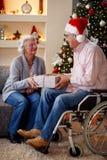Älterer Mann im Rollstuhl und in der Frau mit Weihnachtsgeschenk Lizenzfreie Stockfotos
