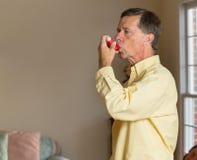 Älterer Mann im Ruhestand mit Asthmainhalator stockfotografie