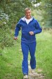 Älterer Mann im Trainingsnazug, der durch Landschaft läuft Stockfotografie