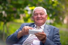 Älterer Mann am intelligenten Mobiltelefon stockfotos