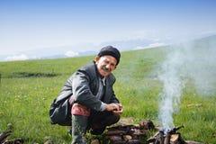 Älterer Mann am Lagerfeuer lizenzfreie stockfotografie