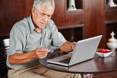 Älterer Mann am Laptop, der mit Kreditkarte zahlt Lizenzfreies Stockbild