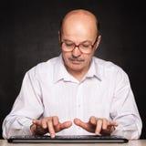 Älterer Mann lernen, auf einer Tastatur mit dem Zeigefinger zu schreiben Lizenzfreie Stockfotografie