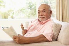 Älterer Mann-Lesebuch mit Getränk zu Hause Stockfotos