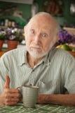 Älterer Mann mit Becher stockfotografie