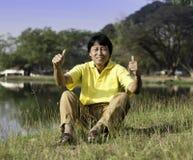 Älterer Mann mit dem Daumen oben gegen einen grünen Park Lizenzfreie Stockfotografie