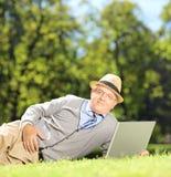 Älterer Mann mit dem Hut, der auf einem grünen Gras liegt und an einem lapt arbeitet Stockbild