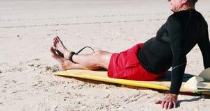 Älterer Mann mit dem Surfbrett, das auf Strand sich entspannt stock video footage