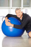 Älterer Mann mit dem Turnhallenball, der hinteres Training tut Stockbilder
