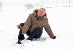 Älterer Mann mit dem verletzten Fahrwerkbein auf Schnee Stockbild