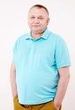 Älterer Mann mit den Händen in den Taschen über Weiß Stockfotos