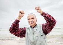 Älterer Mann mit den Händen oben an der Küste lizenzfreie stockbilder