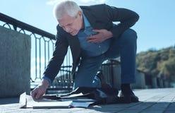 Älterer Mann mit den schweren Herzschmerz, die Dokumente aufheben stockfotografie