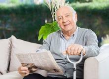 Älterer Mann mit der Zeitung und Stock, die an sitzen Stockfoto