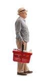 Älterer Mann mit einem Einkaufskorb, der in Linie wartet Stockfotos