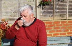 Älterer Mann mit einer Kälte, die seine Nase durchbrennt Lizenzfreies Stockfoto
