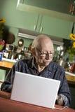 Älterer Mann mit einer Laptop-Computer Lizenzfreie Stockbilder