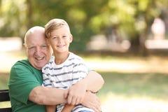 Älterer Mann mit Enkel auf Bank lizenzfreie stockbilder